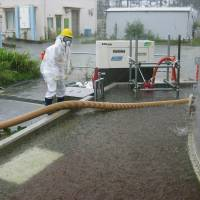 Rain, rain, go away: A worker pumps out radioactive water accumulating inside the barriers around a leaky coolant storage tank at the Fukushima No. 1 nuclear plant Sunday, the day before Typhoon Man-yi swept through Honshu, including the Tohoku region.   | TEPCO/KYODO