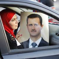 Party line: A Syrian woman holds a portrait of President Bashar Assad as pro-regime supporters celebrate Assad's 48th birthday in Damascus on Tuesday.  | AFP-JIJI