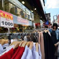 Risky business: Shoppers check out clothes in Tokyo's Harajuku district on Friday. Prime Minister Shinzo Abe's decision this week on the sales tax is a major gamble that history shows could prove his undoing.  | AFP-JIJI