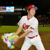 This is for you: Carp ace Kenta Maeda tosses a toy mascot into the stands after his win over the Dragons on Wednesday. | KYODO
