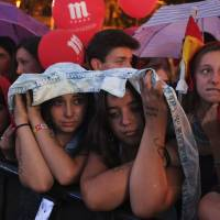 Tearful end: People react at the Puerta de Alcala in Madrid on Saturday after the Spanish capital was eliminated as a host city in voting for the 2020 Olympic Games. | AFP-JIJI