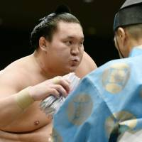 Job well done: Hakuho exhales after winning his bout on Saturday. | KYODO