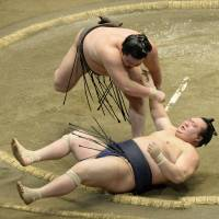 Clear of danger: Hakuho throws Takarafuji to the ground at the Autumn Grand Sumo Tournament on Sunday. | KYODO