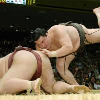 Game over: Hakuho takes down Kisenosato at the Autumn Grand Sumo Tournament on Saturday to win the competition and claim his 23rd career title. | KYODO
