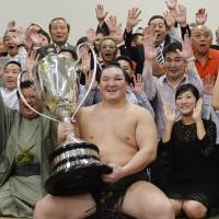 The best in the biz: Yokozuna Hakuho, surrounded by supporters, displays the Emperor's Cup on Sunday a day after clinching his 27th career title. | KYODO