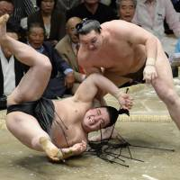 Live to fight another day: Hakuho (right) throws Harumafuji on the final day of the Autumn Grand Sumo Tournament on Sunday. Harumafuji finished with a 10-5 record. | KYODO
