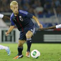 Quick adjustments: Japan's Keisuke Honda tries to move the ball past Ghana's Christian Atsu (7) and Harrison Afful during the first half of Tuesday's match. Honda scored Japan's third goal in the 72nd minute.   KYODO