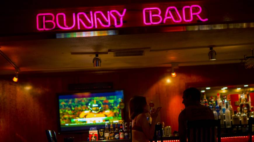 A customer sits with an employee inside the brothel's bar area on Aug. 20.   BLOOMBERG