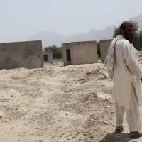 Boxed in: Niaz Mohammad stands on land that was dotted with homes in Tarok Kolache before Americans bombed the village in 2010. Less than half of the village was rebuilt after the bombardment. | THE WASHINGTON POST