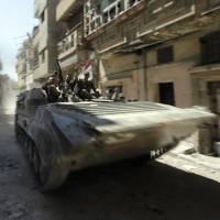 Total war: Syrian government soldiers use a tank to patrol a devastated street in the al-Khalidiyah district of the city of Homs on July 31. | AFP-JIJI