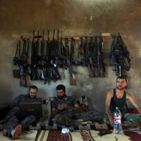 Rebel room: Weapons hang from a wall behind Free Syrian Army fighters in a house on the outskirts of Aleppo, Syria's largest city, in June 2012. | AP