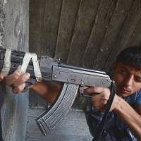 Age of innocence: A young Syrian rebel aims his weapon in the city of Aleppo on Sunday. | AFP-JIJI