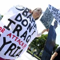 Conflicting views: Anti-war demonstrators protest in front of the White House in Washington on Monday against a possible U.S. attack on Syria in response to possible use of chemical weapons by the regime of President Bashar Assad. | AFP-JIJI