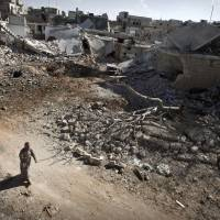 New landscape: A man walks through a destroyed residential area of the Syrian city of Saraqib, southwest of Aleppo, on Tuesday following repeated airstrikes by government forces' fighter jets. | AFP-JIJI