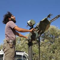 More where that came from: A rebel Syrian fighter fires a heavy machine gun mounted on the back of a pick-up truck during a battle with government forces in the rebel-held northwestern province of Idlib on Monday. | AFP-JIJI