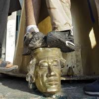 Tarrnished legacy: Rebel fighters trample on a golden head of a Moammar Gadhafi statue inside the Libyan strongman's Bab al-Aziziya compound in Tripoli on in August 2011. | AP