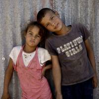 No age of innocence: Syrian siblings pose for a photograph near their tent at a refugee camp in the eastern Lebanese border town of al-Faour on Wednesday. | AP