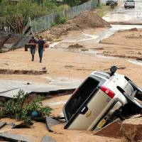 Washed out: New Mexicans survey damage in La Union, where Thursday's flooding destroyed multiple roads in the small town. | AP