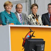 Unauthorized flight: German Chancellor Angela Merkel (left), Christian Democratic Union candidate Arnold Vaatz (second from left), Dresden Mayor Helma Orosz and Defense Minister Thomas de Maiziere look at a camera drone that crash-landed close to where they were standing in Dresden on Sunday. | AP, AFP-JIJI