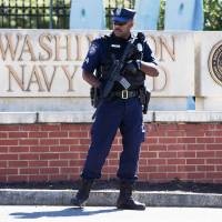 Gatekeeper: A Department of Defense security guard stands watch near the front gate of the Washington Navy Yard on Tuesday. | AP