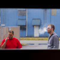 Vapor gets in your eyes: Two men smoke e-cigarettes on a work break.   BLOOMBERG