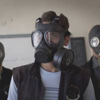 Required class: Syrians wear gas masks in Aleppo while attending a class on how to respond to a chemical attack on Sept. 15. | AFP-JIJI