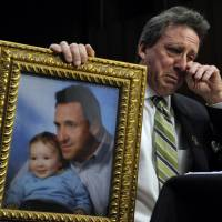 Unspeakable sadness: Neil Heslin, the father of a 6-year-old boy who was slain in the Sandy Hook massacre in Newtown, Connecticut, on Dec. 14, holds a picture of himself with his son, Jesse, while testifying before the Senate Judiciary Committee on Capitol Hill in Washington in February. | AP