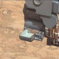 Scratching the surface: The Curiosity rover holds a scoop of powdered rock on Mars before analyzing its chemical makeup in March.   AP