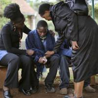 After the attack: A man who lost his father in Saturday's attack by  al-Qaida-linked al-Shabab militants on Nairobi's Westgate Mall is comforted by relatives as he waits for a postmortem exam at the city's morgue Monday. | AP