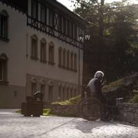 Finding another way: A resident sits in a wheelchair and smokes a cigarette on the grounds of the care home where he lives in Szklarska Poreba, Poland, on Aug. 24. Polish nursing homes have seen a rise in Germans seeking affordable elderly care, while one German newspaper denounced it as 'gerontologic colonialism.' | BLOOMBERG