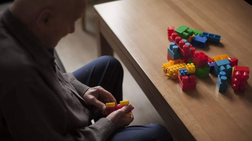 New life: An elderly resident sits at a table and plays with colored building blocks at the nursing home where he lives in Szklarska Poreba, Poland, on Aug. 24. | BLOOMBERG