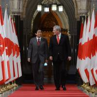 Having a gas: Prime Minister Shinzo Abe and his Canadian counterpart, Stephen Harper, make their way to a joint news conference on Parliament Hill in Ottawa on Tuesday. | AP
