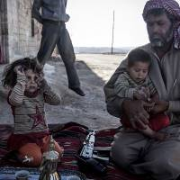 Friend or foe?: A Free Syrian Army fighter holds his son outside their home in Habit, Hama province, on Wednesday. | AP