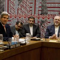 Toned down: U.S. Secretary of State John Kerry and Iranian Foreign Minister Mohammad Javad Zarif (right) attend a meeting Thursday of the five permanent members of the U.N. Security Council plus Germany on Iran's nuclear program, on the fringe of the U.N. General Assembly in New York. | AFP-JIJI