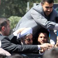 Missed: Bodyguards protect Iranian President Hassan Rouhani (in glasses) after a shoe was thrown at his car in Tehran on Saturday. | AFP-JIJI