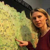 Death map: Lithuanian author Milda Jakulyte-Vasil points to the 'Holocaust Atlas of Lithuania' on Sept. 20 in Vilnius. She runs a bilingual site with an interactive map of where Jews were killed in the country. | AFP-JIJI