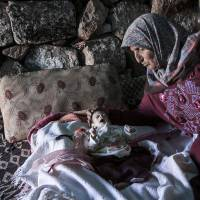 Safe house: A displaced Syrian woman on Friday comforts her 1-month-old grandchild inside a stone dwelling near Kafer Rouma, a site containing ancient ruins. Kafer Rouma is now being used as temporary shelter by families fleeing  heavy fighting and shelling in Idlib province. | AP