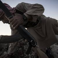 Heads down: A Syrian opposition fighter takes cover during a battle with government forces in Telata village, in northern Idlib province, on Sunday. | AP
