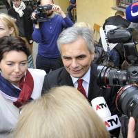 Shoulder to shoulder: Austrian Chancellor Werner Faymann and his wife, Martina Ludwig-Faymann, talk to journalists in a polling station in Vienna on Sunday. The country's two-party centrist coalition will stay in power, but with their worst result ever. | AFP-JIJI