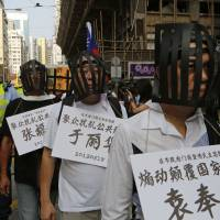 Muzzled: Pro-democracy activists demonstrate for jailed Chinese dissidents on Tuesday in Hong Kong, demanding their release.   AP
