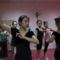 Big payout?: Ma Qianyi, 12 (left foreground) dances as part of a three-hour lesson she attends after a full school day in Beijing; instruction has cost $5,000 over six months, but her mother hopes Qianyi's talent will help get her into an elite school. | THE WASHINGTON POST