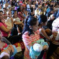 Abreast of the times: Mothers hold their children prior to a simultaneous nationwide breast-feeding event in Marikina, suburban Manila, on Thursday in an attempt to break a world record and raise public awareness of human milk consumption. | AFP-JIJI