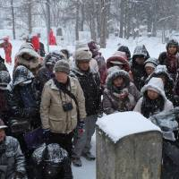 Commemoration: Members of the Takiji-sai, a group of admirers of late proletarian writer Takiji Kobayashi, gather at his grave in Otaru on Feb. 20, the 80th anniversary of his death. | DREUX RICHARD