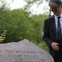 Entombed: Kyoto University nuclear physicist Hiroaki Koide takes radiation readings with a Geiger counter at a stone marker indicating the burial site of the world's first nuclear reactor at Red Gate Woods outside Chicago in May 2012. | DREUX RICHARD