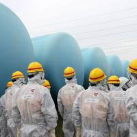 Ongoing problem: Workers examine a row of water storage tanks at the Fukushima No. 1 nuclear power plant on Aug. 23. | BLOOMBERG
