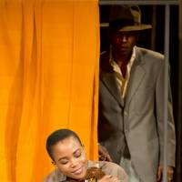 Sizing up: Matilda (Nonhlanhla Kheswa) hugs her lover's suit he left behind as he fled, but which her watching husband Philomen (William Nadylam) has turned into a punishment for her.   © JOHAN PERSSON