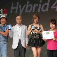 Standing out: Softbank Corp. President Masayoshi Son (second from left) and others show the firm's new winter and spring lineup of phones and other products during a news conference in Tokyo on Monday. | KAZUAKI NAGATA