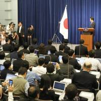 Photo op: Prime Minister Shinzo Abe poses for photographers before starting a news conference Tuesday to explain his decision to raise the consumption tax. | AP