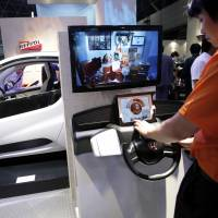 Take it for a spin: An assistant at a Honda Motor Co. booth uses a tablet device to demonstrate a remote control system for operating home electronics equipment, near the firm's electric vehicle (left) at the CEATEC exhibition in Chiba Prefecture on Tuesday. | BLOOMBERG