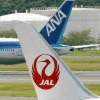 Cross-check: A Japan Airlines plane and an All Nippon Airways aircraft taxi near each other at Narita International Airport in September 2012.   KYODO